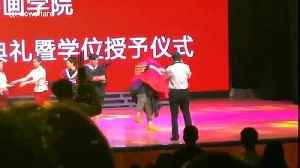 Excited graduate in China falls over on stage with university president in his arms [Video]