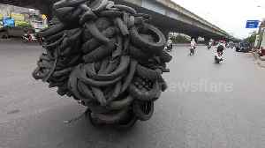 Hundreds of tyres are balanced on motorbike as it drives down road in Vietnam [Video]