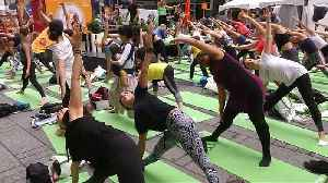Rain doesn't stop yogis from celebrating the summer solstice in Times Square [Video]