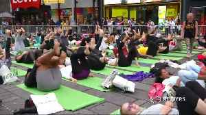 Rain can't stop yogis from celebrating the summer solstice in Times Square [Video]