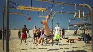 Man Works Through Obstacle Course on Monkey Bars at Beach [Video]