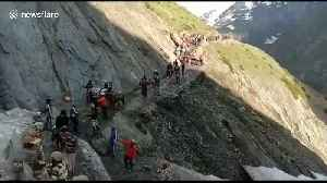 Indian officers form human shield to protect pilgrims from falling rocks [Video]
