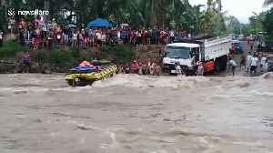 Passengers watch on as bus flips over in raging river in the Philippines [Video]