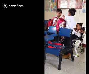 Touching moment two Filipino schoolboys help their classmate with cerebral palsy during break time [Video]