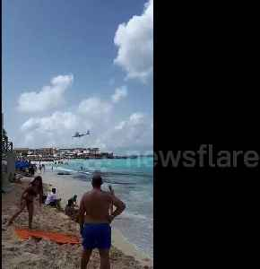 Beachgoers watch as planes fly low over Caribbean beach [Video]