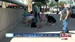 Chalk protests in front of City Hall [Video]