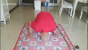 Elderly Chinese man headstands while practising calligraphy with his foot [Video]