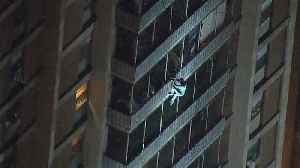Video shows man climb down building during fire in Philadelphia