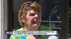 Woman burns book to draw attention to priest sex abuse allegations [Video]