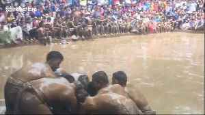 Lads in loincloths battle for a ball in Vietnamese mud game [Video]
