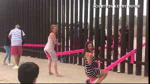 People play on pink seesaws at border wall [Video]