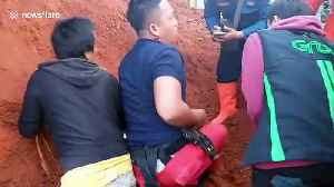 Rescuers battle to reach family trapped in car crushed by overturned lorry in Indonesia [Video]