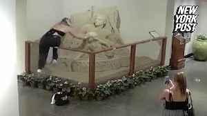 Tube top-wearing vandal destroys sand sculpture [Video]