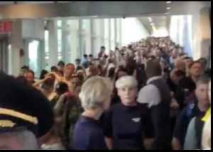 Travelers Crowd Hallway at New York's JFK Airport During Customs System Outage [Video]