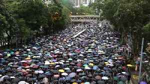Protesters shout 'Hong Kong People, go for it!' as they march through rain-soaked streets [Video]
