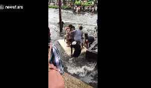 Women float on polystyrene board across road flooded by Storm Bailu [Video]