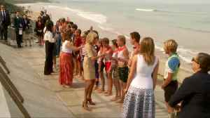 G7 first ladies exchange high-fives with Biarritz surfers at beach [Video]