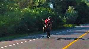 Motorcyclist casually rides down highway on back wheel [Video]