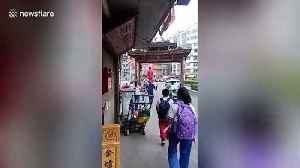 Girl balances on grandfather's shoulders while being taken to school [Video]