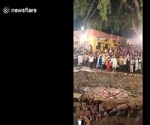 Indian devotee jumps into fire pit and tosses hot embers in air with bare hands [Video]