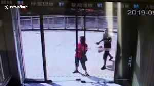 Glass door shatters on people after they attempt to stop it from falling over in China [Video]