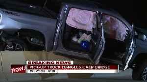 Pick-up truck dangles over bridge [Video]