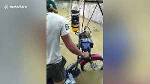 Mechanics have wacky modified motorcycle for riding through floods [Video]