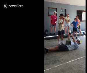 Australian science teacher performs controversial physics experiment letting student smash concrete block on his chest with sled [Video]