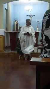 Curious Dog Plays With Priest's Robe While he Gives Speech Inside Church [Video]