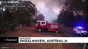 Australian firefighters run to avoid bushfire