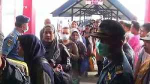 Passengers travelling from Malaysia into Indonesia are scanned for coronavirus symptoms [Video]