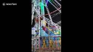 India fairground staff perform nerve-wracking stunt by hanging onto Ferris wheel as it spins around at speed [Video]