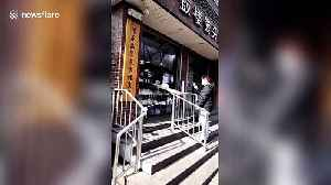 Beijing shop uses DIY slide to hand over food at safe distance amid coronavirus outbreak [Video]