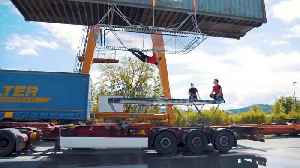 Slovenian acrobats perform daring stunts on trampoline attached to moving truck and shipping container [Video]