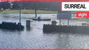 Hilarious moment man is seen kayaking through flooded car park [Video]