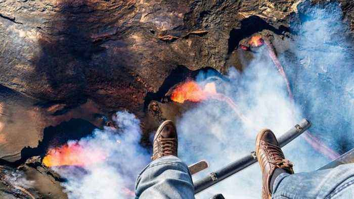 It's getting hot up here: Adventurous photographer dangles dangerously above erupting volcano for up-close glimpse of fear
