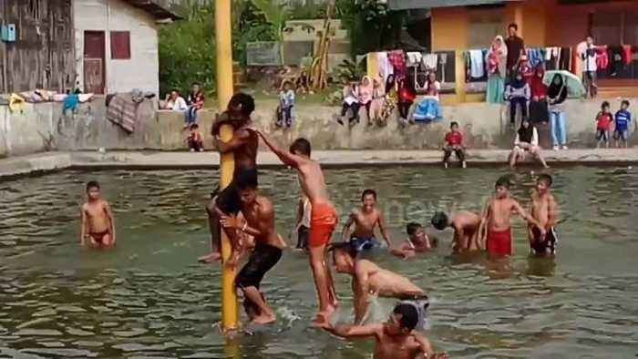 Bizarre pole-climbing ritual sees Indonesian men test agility and strength for prizes