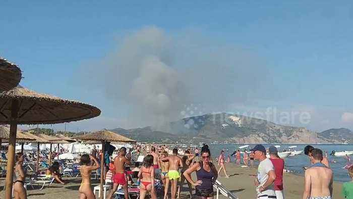 Wildfire burning in distance doesn't ruin day for beachgoers on Greek island