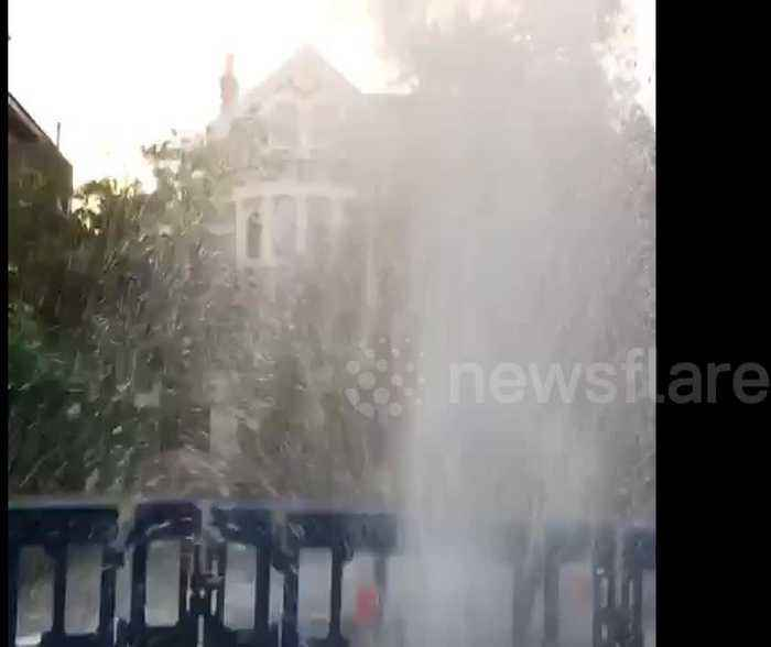 Burst water main sprays water into the air on residential London road