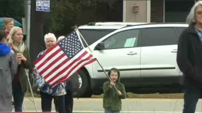 Pint-sized patriot holds flag as he waits for George H.W. Bush's funeral train to pass by
