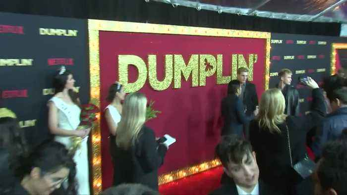 Dolly Parton and Jennifer Aniston walk the carpet at Dumplin world premiere