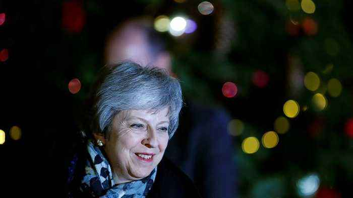 May heads for Brussels after surviving rebels' challenge