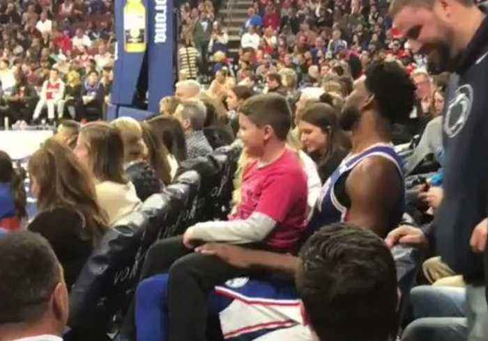 In the Lap of the Gods... Joel Embiid Lets Young Fan Sit on His Knee During Sixers Win