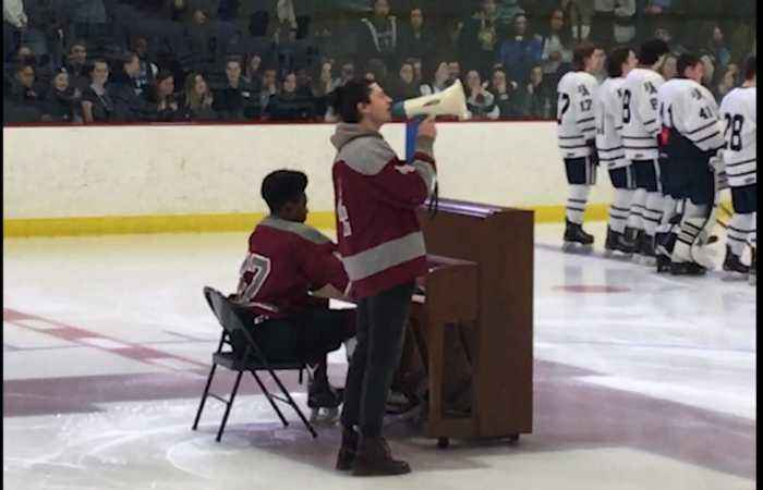 High school hockey player performs national anthem on piano in full uniform