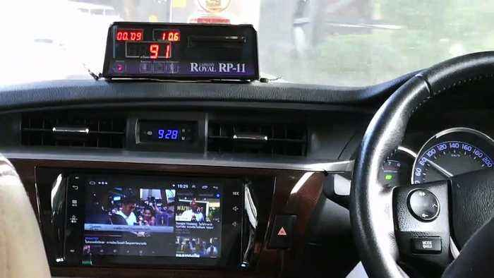 Bangkok taxi driver watches TV in his modified dashboard