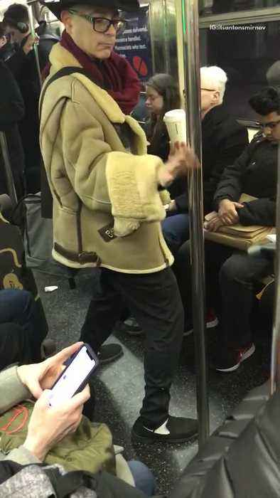 Man kung fu fights with pole inside of subway train
