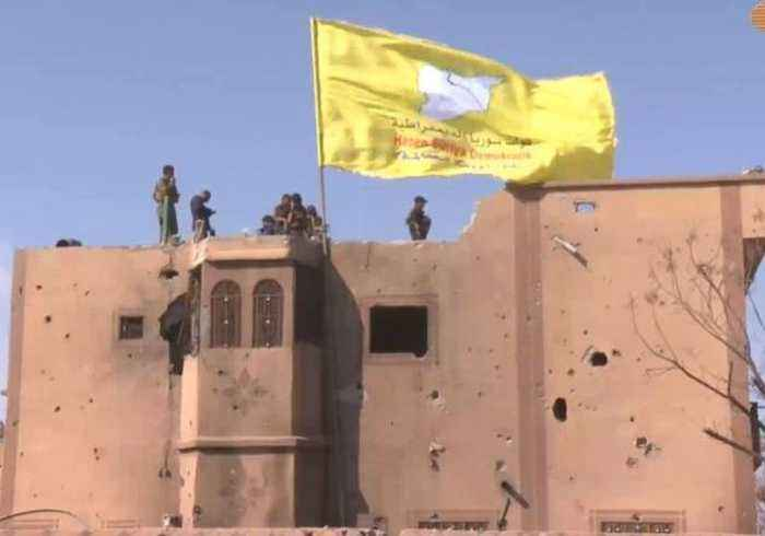 SDF Flag Raised Over Building as US-Backed Group Reports Victory Over Islamic State in Baghuz