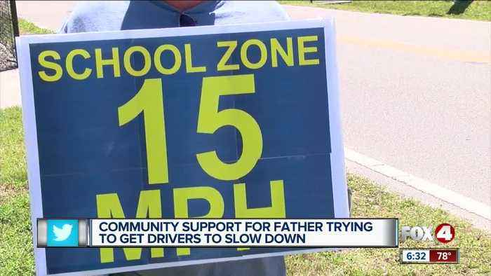 Father making an impact with signs asking drivers to slow down near school