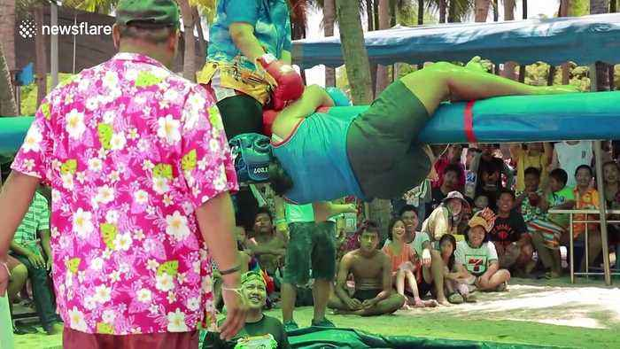 Thai youngsters engage in boxing match whilst balancing on pole above pool