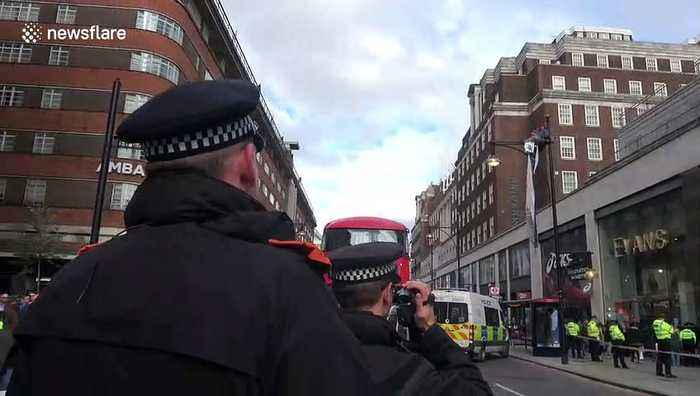 Man climbs lamppost in London's Oxford Street in climate change protest